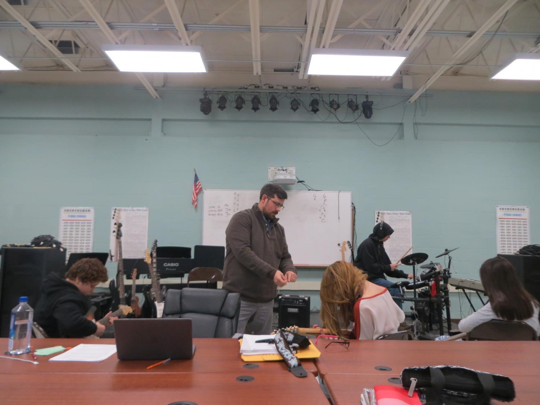 Mr. Veiga teaches bass guitar to a recent music class.