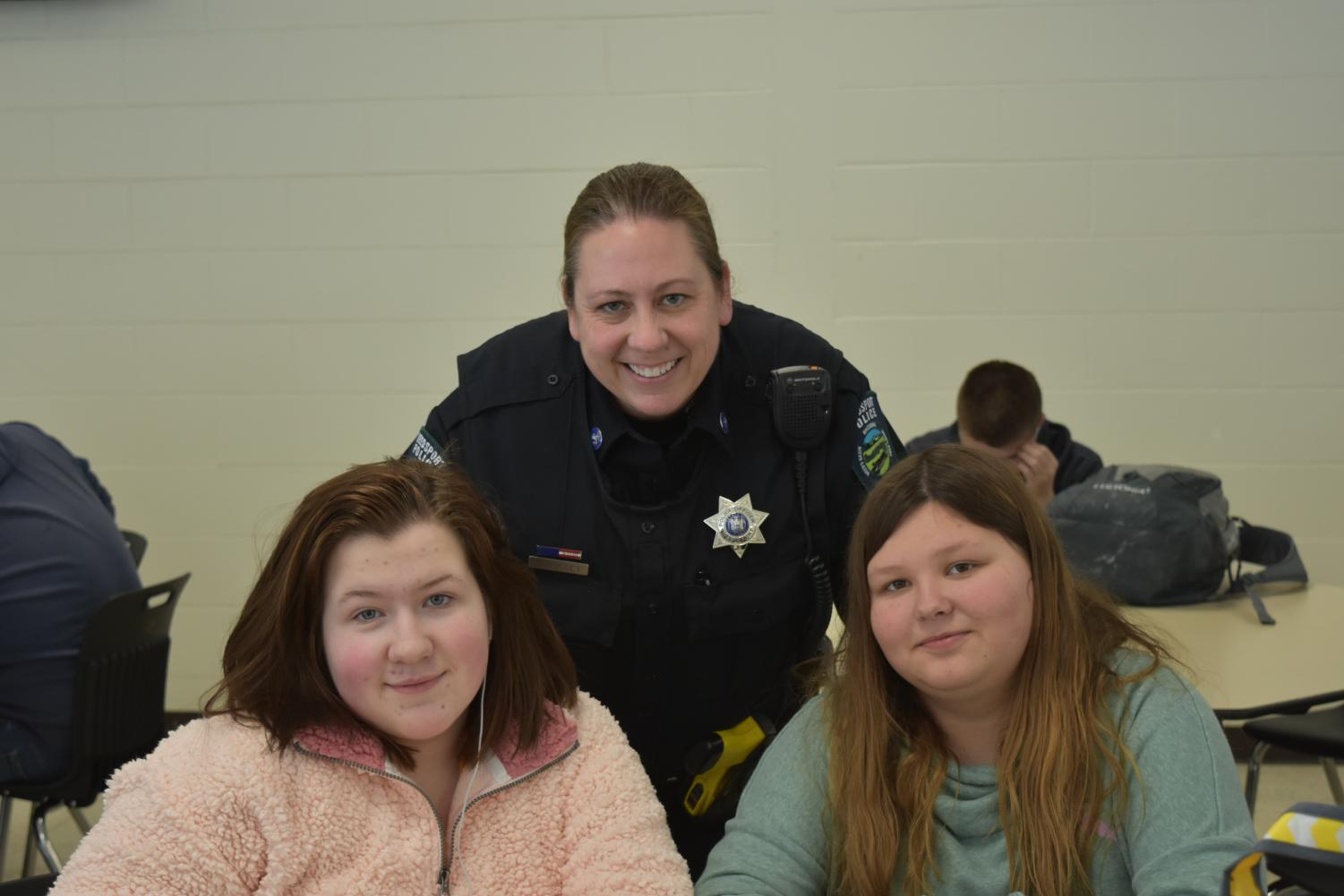 Officer Quigley takes a moment out of her day to share a smile with Weedsport freshmen Maddie Higgins and Brooklyn Smith.